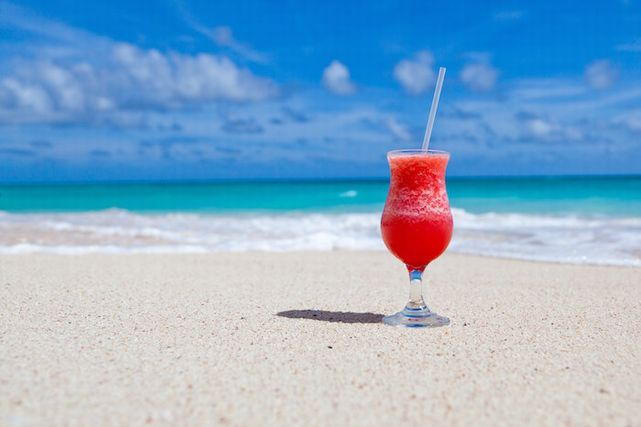 白い砂浜に置かれたドリンクのグラス