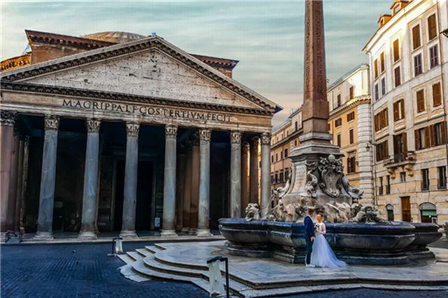 ローマの街に立つウエディングドレスとタキシード姿のカップル