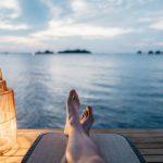 海を見ながら寝そべる女性の足