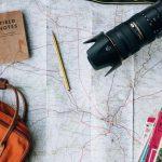 世界地図の上に置かれたカメラやバッグ