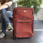 女性の横に置かれたソフトタイプのスーツケース