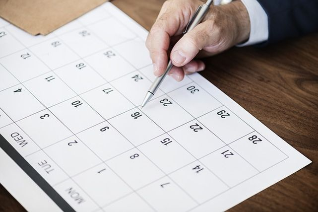カレンダーを指さす男性の手