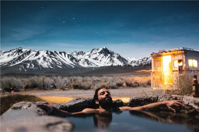 星空の下、温泉に入る外国人男性