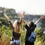 山の頂上で両手を上げる2人の女性