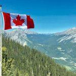 カナディアンロッキーを背景に立てられたカナダの国旗
