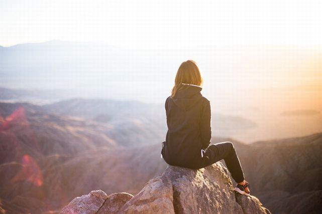 岩に座り景色を眺める女性